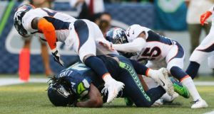 Marshawn Lynch is tackled in the end zone for a safety by Denver's T.J. Ward, left, and Chris Harris on Sept. 21 (AP)