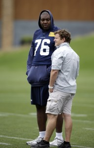 Russell Okung talks with GM John Schneider during minicamp in June (AP)