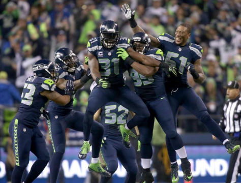 Teammates mob Kam Chancellor (31) after his stunningly stellar stunt on a field goal attempt seemed to succeed vs. Carolina (Seahawks.com)